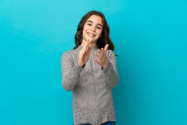 Маленькая кавказская девушка изолирована на синей стене аплодирует после презентации на конференции