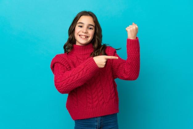 늦게되는 제스처를 만드는 파란색 벽에 고립 된 어린 백인 소녀