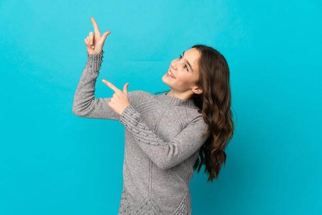 人差し指で指している青い壁に孤立した小さな白人の女の子素晴らしいアイデア
