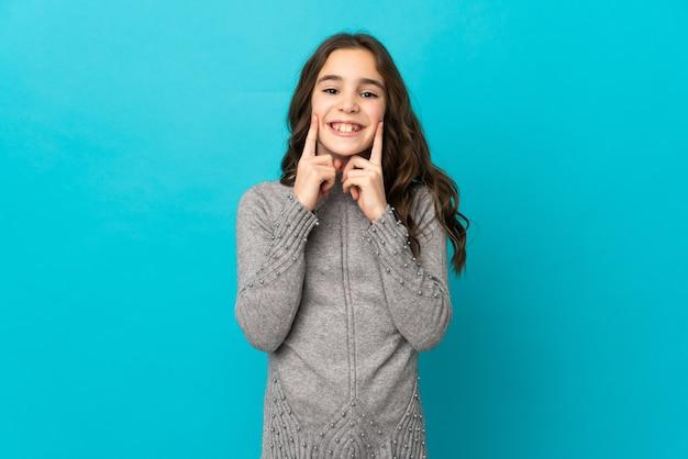 행복하고 즐거운 표정으로 웃고 파란색 벽에 고립 된 어린 백인 소녀