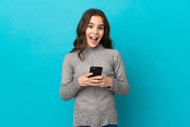 파란색 벽에 고립 된 어린 백인 소녀 놀라게 하 고 메시지를 보내는