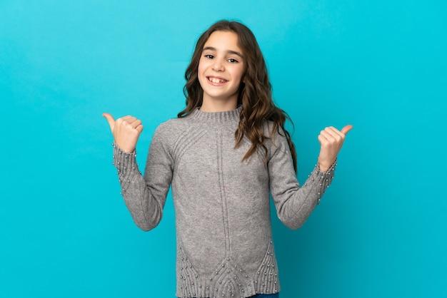 엄지 손가락 제스처와 웃는 파란색 벽에 고립 된 어린 백인 소녀