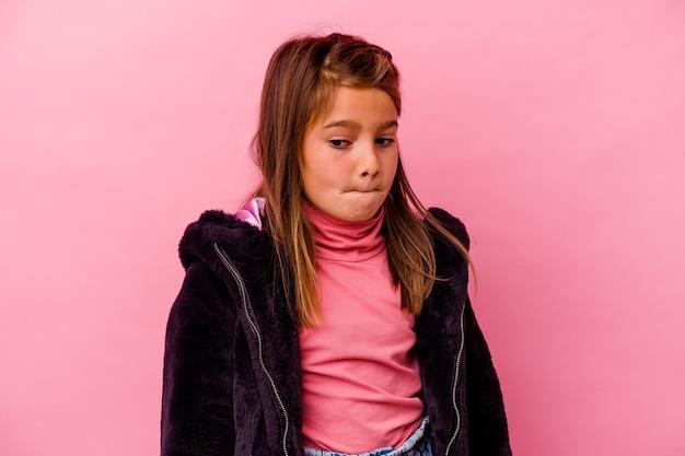 ピンクの背景に孤立した小さな白人の女の子は混乱し、疑わしく、不安を感じます。