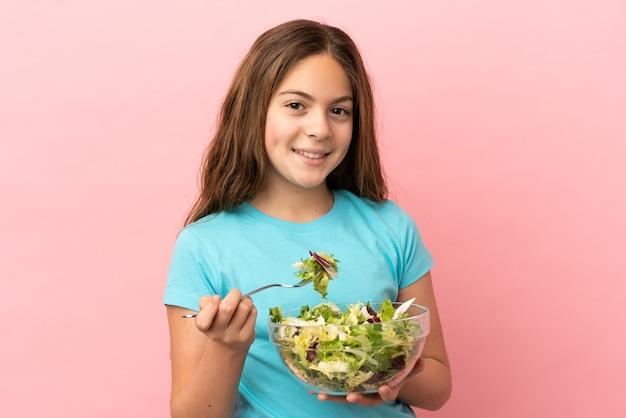 幸せな表情でサラダのボウルを保持しているピンクの背景に分離された白人の少女
