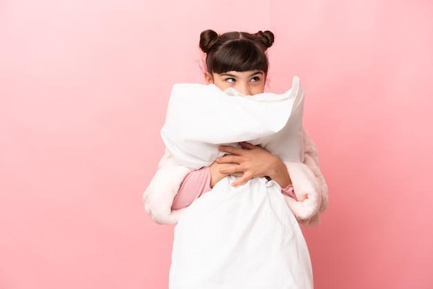 잠옷에 분홍색 배경에 고립 베개를 들고 어린 백인 소녀