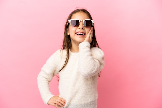 Маленькая кавказская девочка, изолированная на розовом фоне, кричит с широко открытым ртом