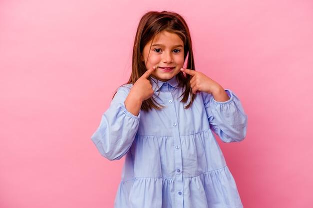 입에 손가락을 가리키는 분홍색 배경 미소에 고립 된 어린 백인 소녀.