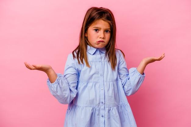 Маленькая кавказская девушка изолирована на розовом, смущенном и сомнительном пожимании плечами, чтобы удержать копию пространства.