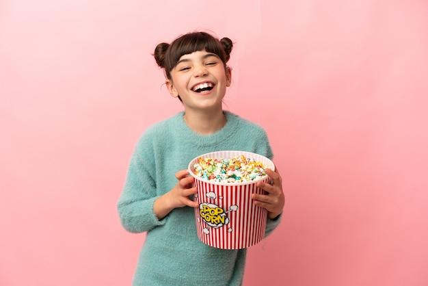 Маленькая кавказская девушка изолирована на розовом с большим ведром попкорна