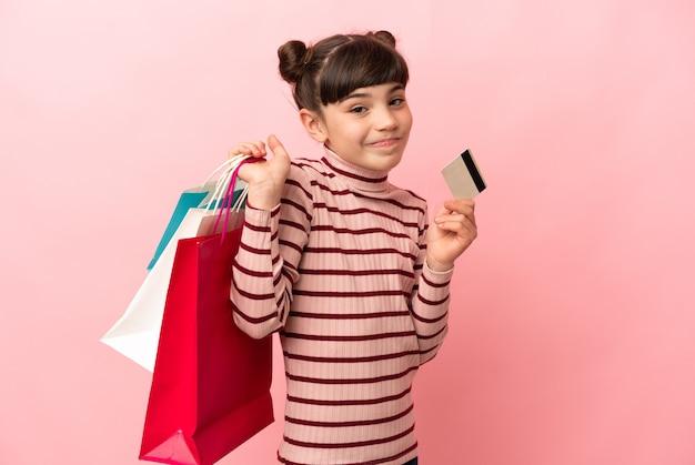 ショッピングバッグとクレジットカードを保持しているピンクで隔離の小さな白人の女の子