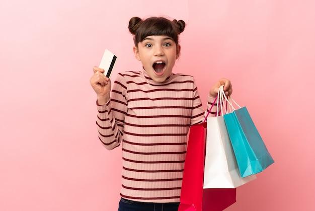 ピンクの買い物袋を持って孤立し、驚いた白人の少女
