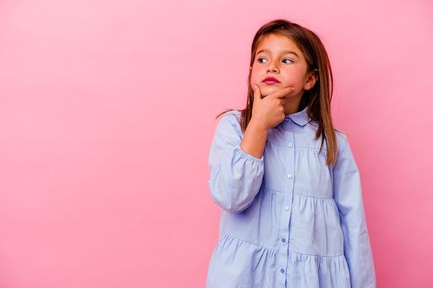 Маленькая кавказская девушка изолирована на розовом, глядя в сторону с сомнительным и скептическим выражением лица.