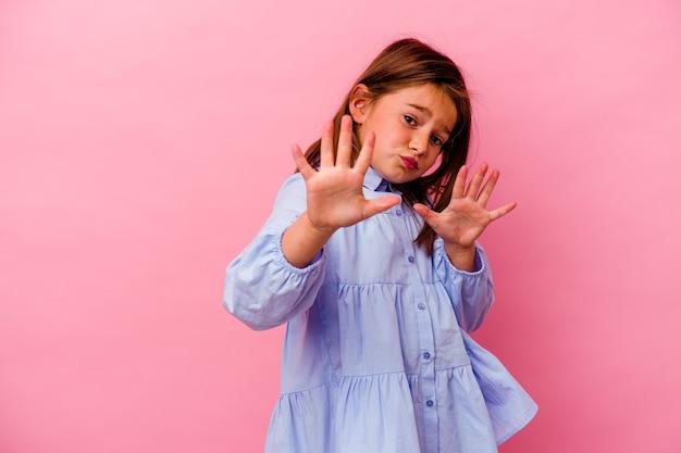 Маленькая кавказская девушка изолирована на розовом, отвергая кого-то, показывая жест отвращения.