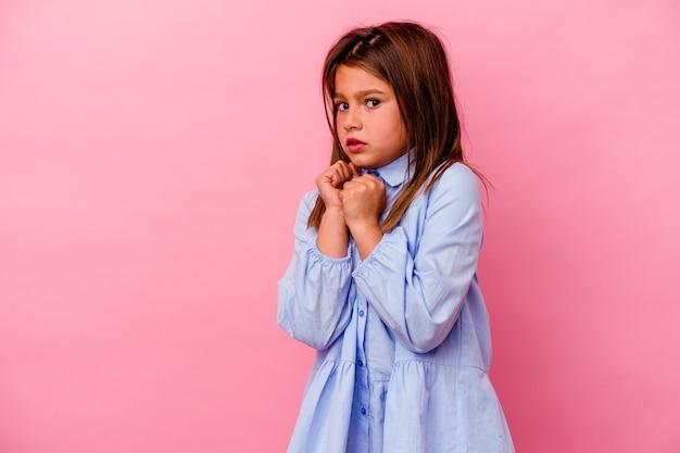Маленькая кавказская девочка, изолированная на розовом, испугалась и испугалась.