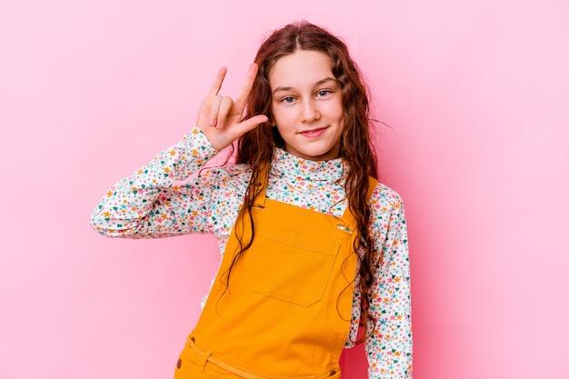革命の概念として角のジェスチャーを示すピンクで隔離された小さな白人の女の子。