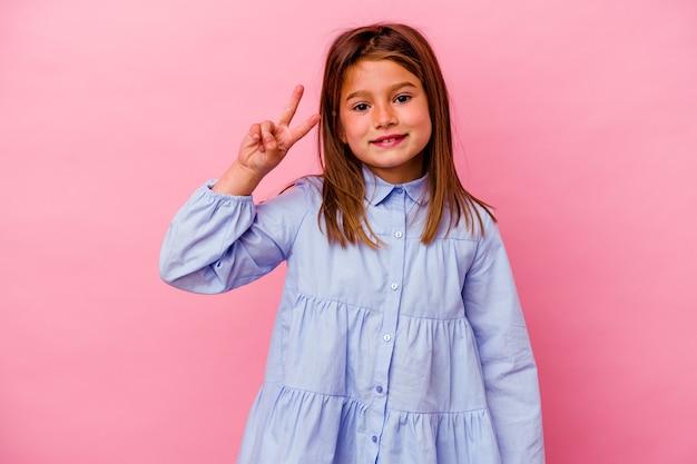 Маленькая кавказская девушка изолирована на розовом, показывая знак победы и широко улыбаясь.