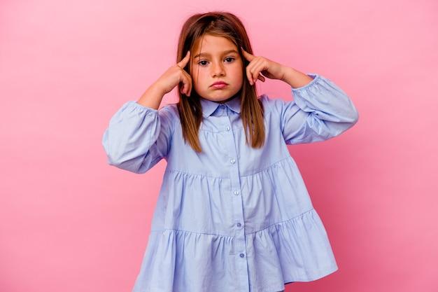 분홍색 벽에 고립 된 어린 백인 소녀는 머리를 가리키는 집게 손가락을 유지하는 작업에 집중했습니다.
