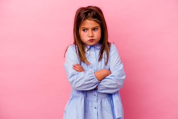 불만에 얼굴을 인상을 찌푸리고 분홍색 벽에 고립 된 어린 백인 소녀, 팔을 접혀 유지합니다.