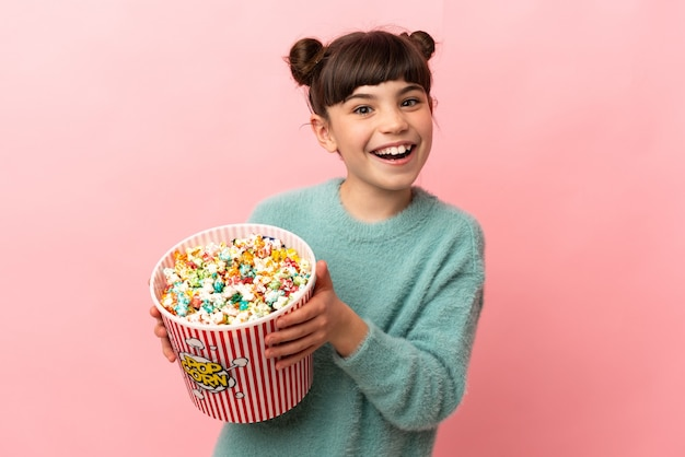 Маленькая кавказская девушка изолирована на розовой стене, держа большое ведро попкорна