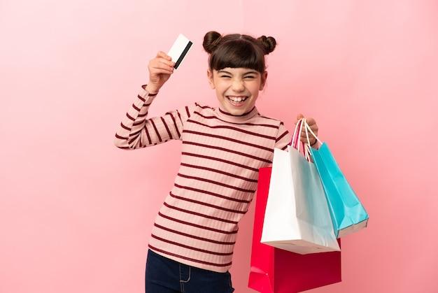 ショッピングバッグとクレジットカードを保持しているピンクの壁に分離された白人の少女
