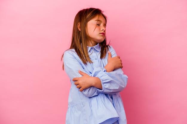 Маленькая кавказская девушка, изолированная на розовых стенах, обнимает, беззаботно улыбается и счастлива.