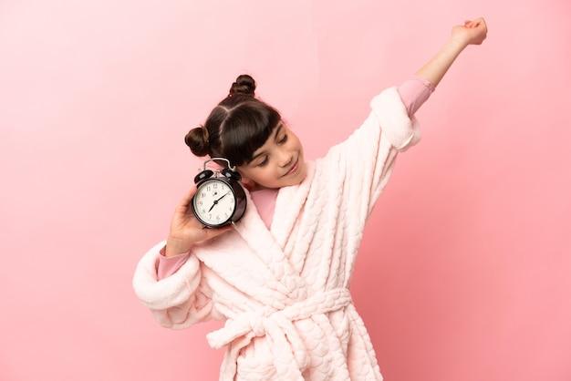 잠옷에 분홍색 벽에 고립 된 어린 백인 소녀와 승리 제스처를 하 고 시계를 들고