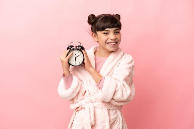 잠옷에 분홍색 벽에 고립 된 어린 백인 소녀와 행복한 표정으로 시계를 들고