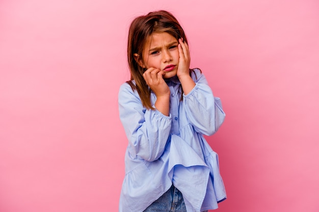 Маленькая кавказская девушка изолирована на розовой стене ныть и безутешно плачет.