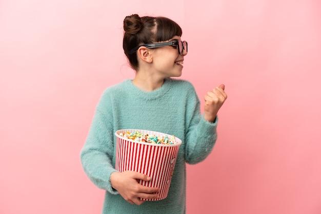 Маленькая кавказская девушка изолирована на розовой стене в 3d-очках и держит большое ведро попкорна, глядя в сторону