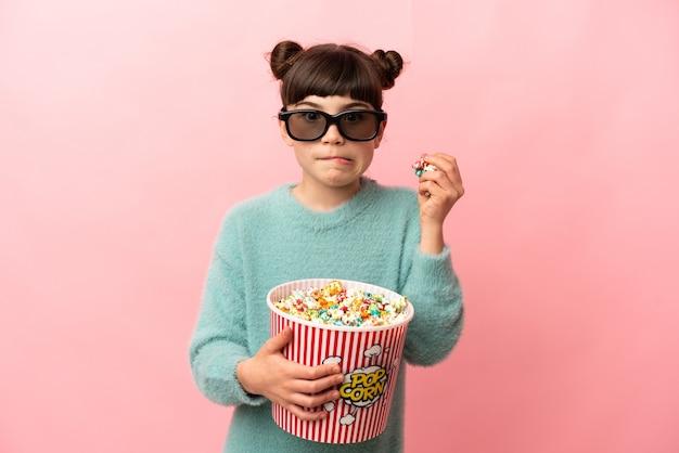 3dメガネでピンクの壁に隔離され、ポップコーンの大きなバケツを保持している小さな白人の女の子