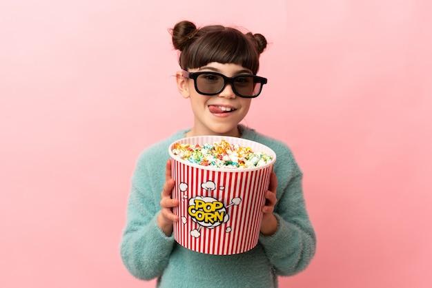 Маленькая кавказская девушка изолирована на розовой стене в 3d-очках и держит большое ведро попкорна