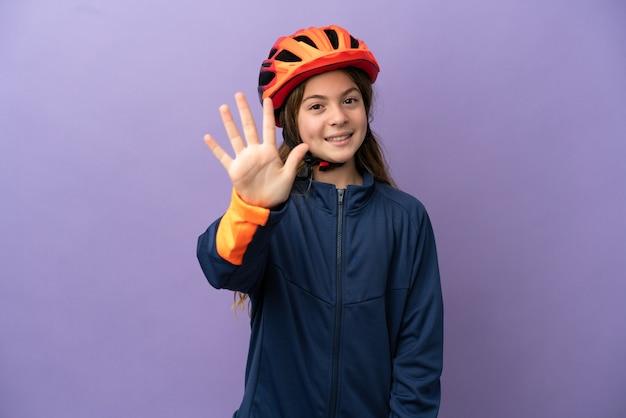 Маленькая кавказская девушка изолирована на фиолетовом фоне, считая пять пальцами