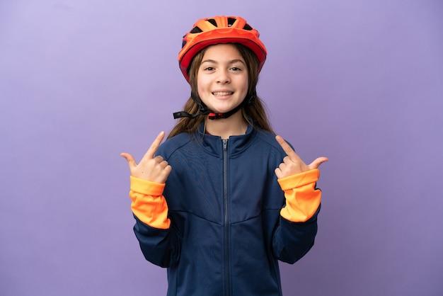 Маленькая кавказская девушка изолирована на фиолетовом фоне, показывая большой палец вверх жест