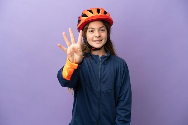 Маленькая кавказская девушка изолирована на фиолетовом фоне счастлива и считает четыре пальцами