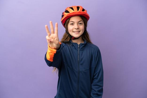 Маленькая кавказская девушка изолирована на фиолетовом фоне счастлива и считает три пальцами