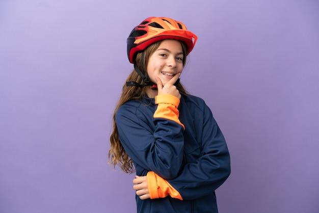 Маленькая кавказская девочка, изолированные на фиолетовом фоне, счастлива и улыбается