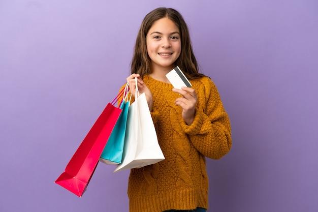 Маленькая кавказская девушка изолирована на фиолетовом фоне, держа хозяйственные сумки и кредитную карту