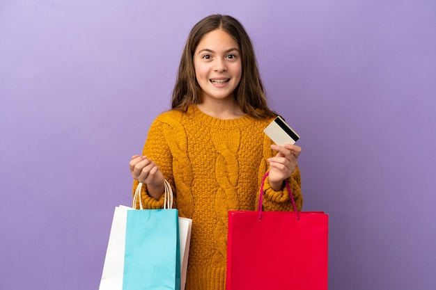 보라색 배경에 격리된 백인 소녀가 쇼핑백을 들고 놀란다