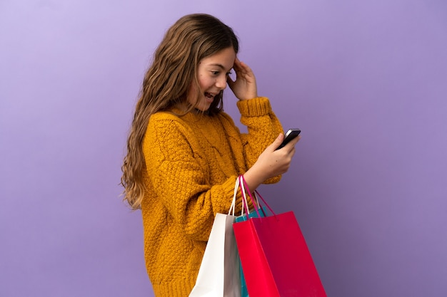 보라색 배경에 격리된 백인 소녀는 쇼핑백을 들고 친구에게 휴대전화로 메시지를 씁니다.