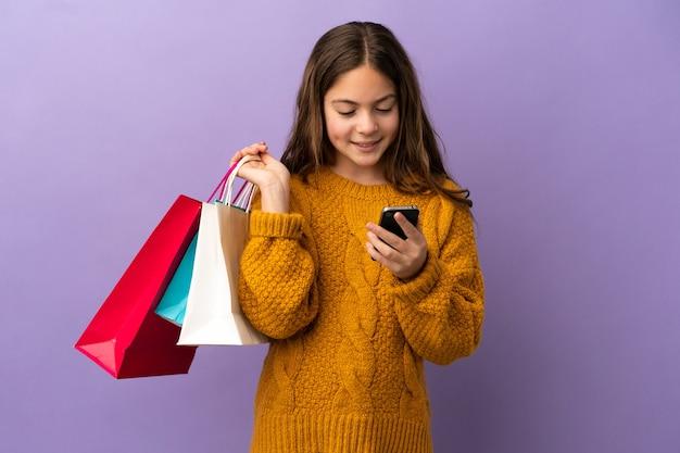Маленькая кавказская девушка изолирована на фиолетовом фоне, держа хозяйственные сумки и пишет сообщение со своим мобильным телефоном другу