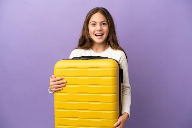 Маленькая кавказская девушка изолирована на фиолетовом фоне в отпуске с чемоданом и удивлена