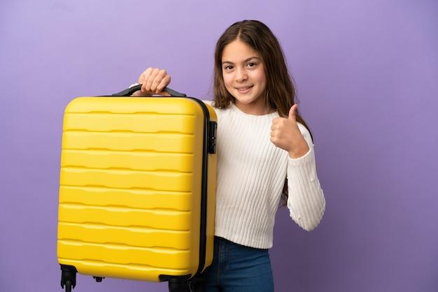 Маленькая кавказская девушка изолирована на фиолетовом фоне в отпуске с чемоданом и с большим пальцем вверх