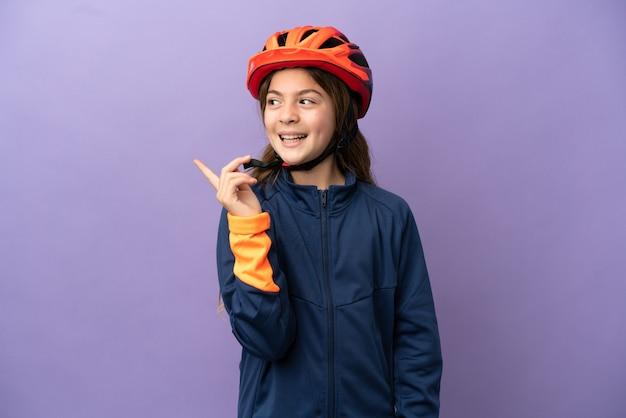 Маленькая кавказская девушка изолирована на фиолетовом фоне, намереваясь понять решение, подняв палец вверх