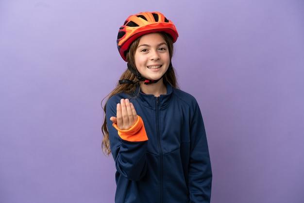 Маленькая кавказская девушка, изолированные на фиолетовом фоне, приглашая прийти с рукой. счастлив что ты пришел
