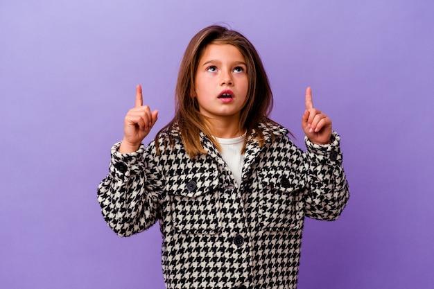 보라색 배경에 고립 된 어린 백인 소녀 열린 된 입으로 거꾸로 가리키는 보라색 배경에 고립 된 어린 백인 소녀.
