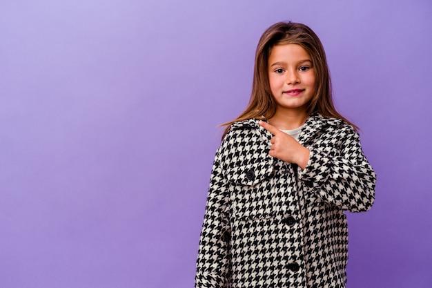 紫色の背景に孤立した小さな白人の女の子紫色の背景に孤立した小さな白人の女の子笑顔と脇を指して、空白のスペースで何かを示しています。