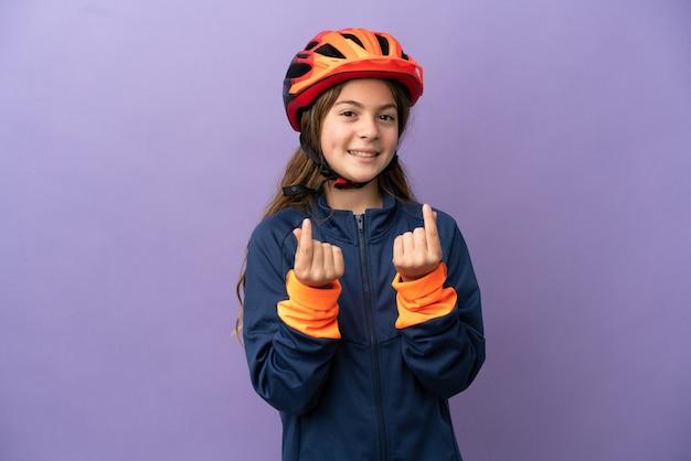 Маленькая кавказская девушка изолирована на фиолетовом фоне, делая денежный жест