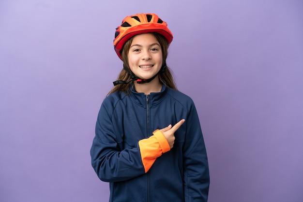제품을 제시하기 위해 측면을 가리키는 보라색 배경에 고립 된 어린 백인 소녀