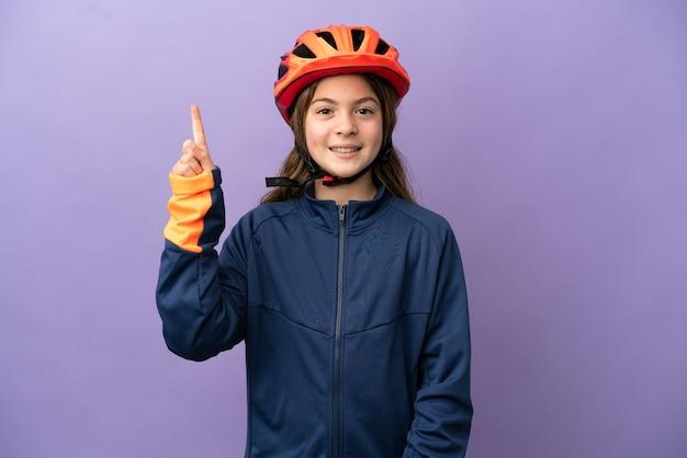 좋은 아이디어를 가리키는 보라색 배경에 고립 된 어린 백인 소녀