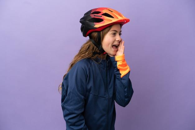 Маленькая кавказская девочка, изолированная на фиолетовом фоне, кричит с широко открытым ртом в сторону